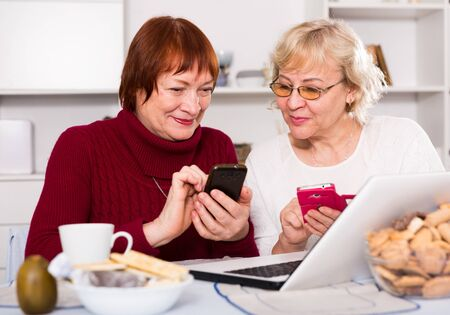 Smiling pensioners females talking at kitchen holding mobile phones Stock Photo