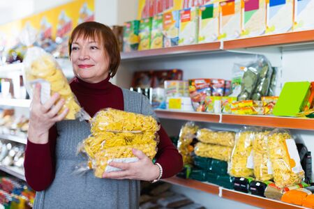 Adult positive female buyer  choosing packaging of pasta in the food store Foto de archivo - 129914053