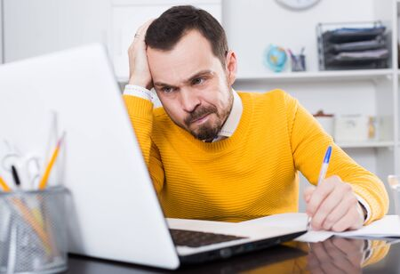 Man in yellow shirt at office of serious documents on laptop computer