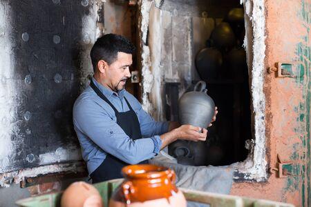 Smiling mature man potter holding black glazed ceramic vessel next to kiln