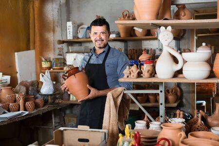 Smiling man artisan having ceramics in hands and standing in workshop