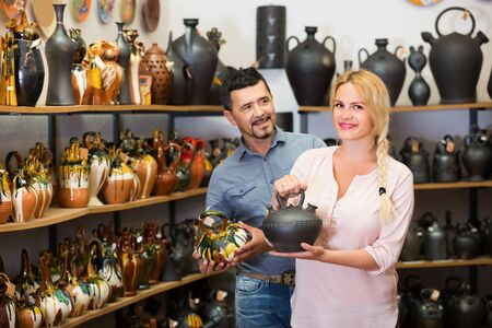 portrait of happy spanish man and woman shopping ceramic utensil in boutique Stock Photo