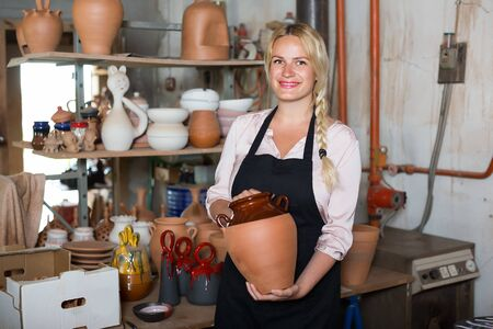 Woman potter in apron carrying ceramic vessels in atelier