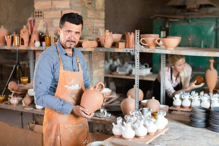 joyful smiling male potter holding ceramics in hands in ceramics atelier Stock Photo