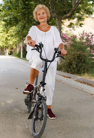 Smiling mature woman standing near bicycle ready to go on city ride