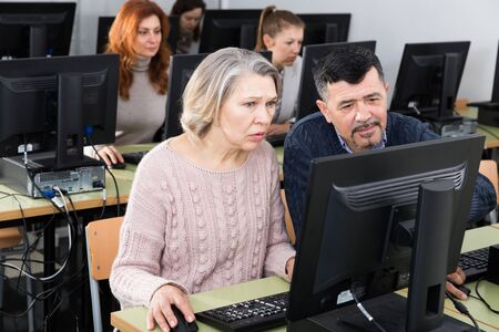 Computer lessons for adults. Friendly mature man and woman learning together to use computer in classroom with group Stockfoto