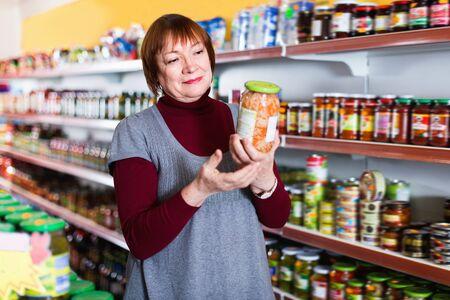 Adult cheerful positive glad female customer holding glass jar of sauerkraut in the supermarket Foto de archivo - 129914189