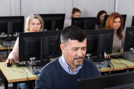 Portrait of focused mature man during computer classes at university of third age Stockfoto