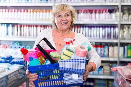 Mature buyer holding basket with chemical products for cleaning house in shop