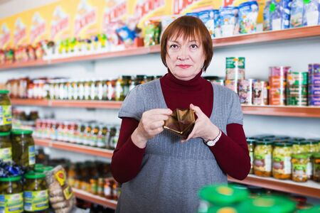 Sad woman buyer with empty purse and canned at the supermarket Foto de archivo - 129914458