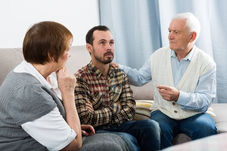 Aged grandparents and grandson are serious conversation at home and solve problems Stock fotó