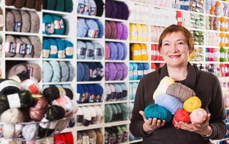 Female with colorful yarn during shopping in needlework shop