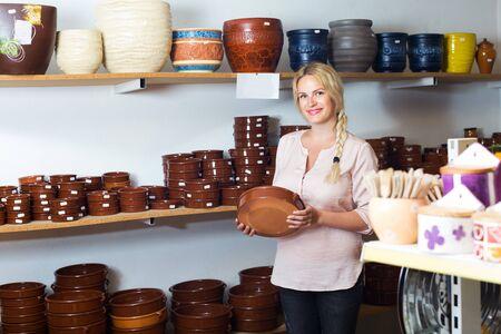 Portrait of glad girl choosing ceramic utensil in boutique