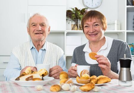 Smiling elderly husband and wife having breakfast and talking at table Banque d'images