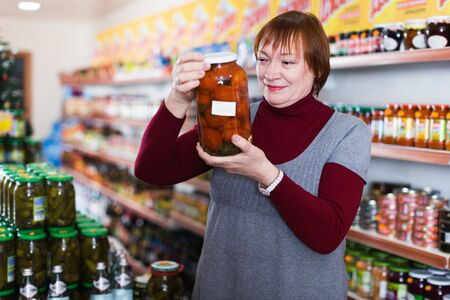 Mature woman in the store choosing preserved food of tomatoes