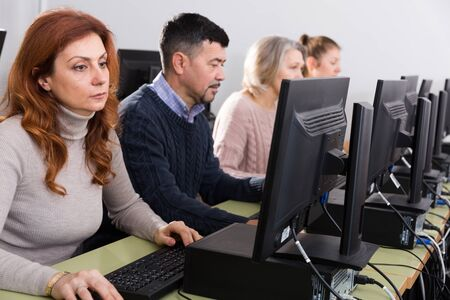Portrait of modern elderly people working on computers while attending pc class