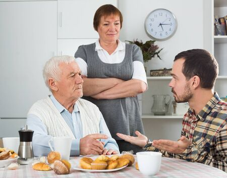 Aged grandfather teaches and instructs his grandson at table at home Stock fotó