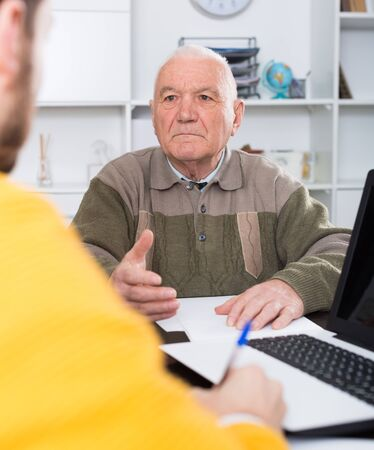 Elderly man and agent sign life and health insurance contract  in office