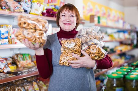 Portrait of smiling mature woman buying bakery products in the food store Foto de archivo - 129914548