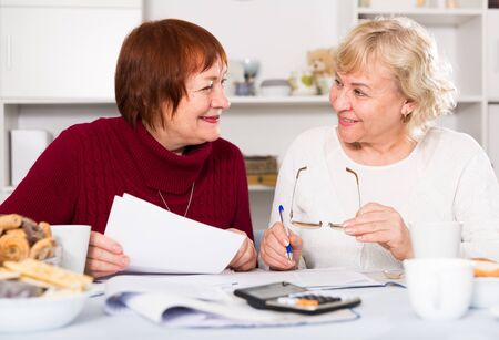 Smiling pensioners females at the table with utilities bills at home Stock Photo