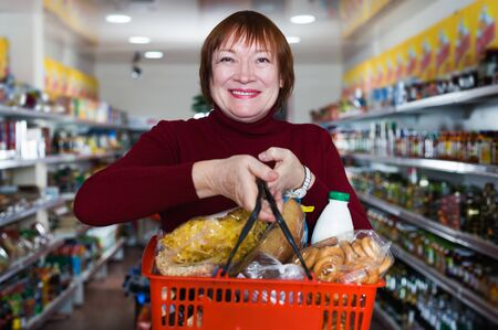Smiling mature woman consumer in the supermarket choosing food with basket Foto de archivo - 129914596