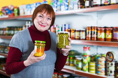 Aged positive female in the shop holding preserved jar of peas Foto de archivo - 129914605