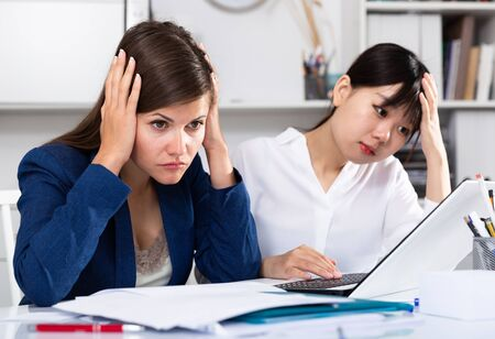 Women reading documents with upset faces at office