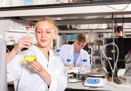 Attractive female student performing experiments in university laboratory, examining chemical substances in glass lab flask
