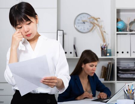 Boss dismissing an employee. Chinese woman crying in company office 写真素材