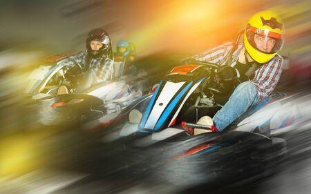 Young positive people in helmets driving go-kart cars in sport club 版權商用圖片