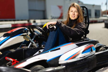 Young female sitting in car for karting in sport club outdoor Stockfoto