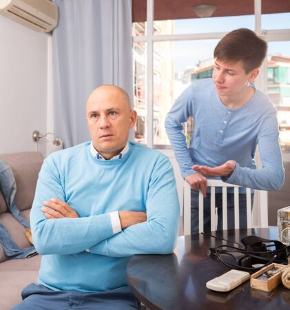 Teen boy trying to apologize his irritated father after dispute Stock Photo