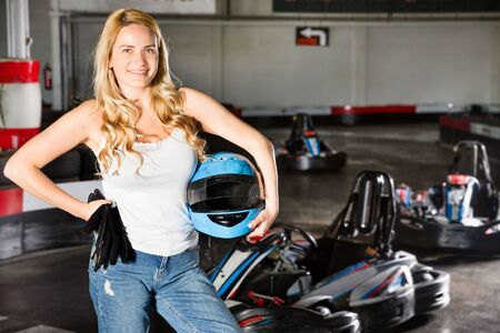 Portrait of female racer holding helmet in her hand at kart track