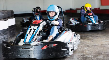 Young smiling people driving sport cars for karting in a circuit lap in sport club