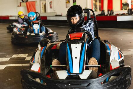 Portrait of female racer in helmet driving a kart on the track