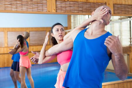 Woman is training with man on the self-defense course in gym