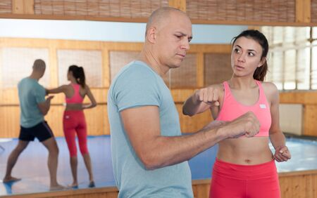 Womens self-defense workout with personal trainer, fighting training in gym Stockfoto