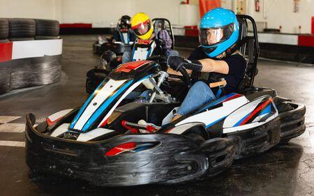 Portrait of female racer in helmet driving kart at a track