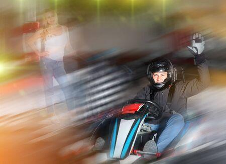 Portrait of happy man finishing race at kart circuit