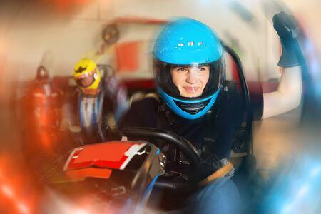 Portret van actieve gelukkige vrouw raceauto rijden op kart circuit