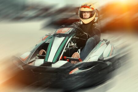 Young positive female in helmet driving car for karting in sport club outdoor