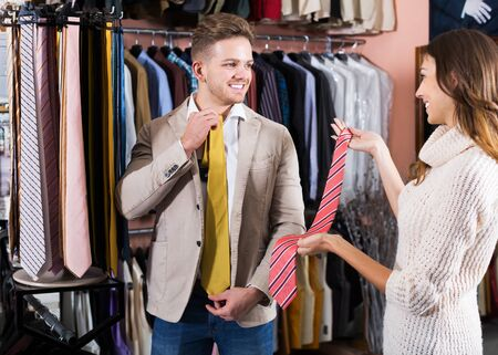 Young positive couple deciding on tie in men's clothes store Foto de archivo - 130050953