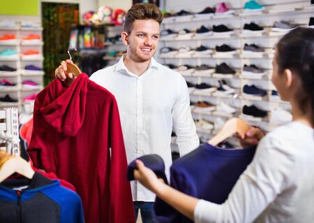 Smiling  positive couple choosing new sportswear in sports store