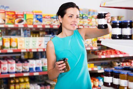 Smiling woman choosing jar of fruit jam at the modern supermarket