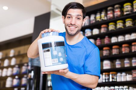 Adult athletic guy showing big pot of sport nutrition products in store Stockfoto