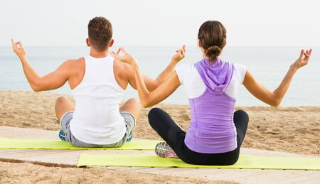 Positive young couple training yoga poses on beach on sunny morning
