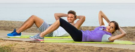 Young cheerful smiling couple do exercises on beach by ocean at daytime 版權商用圖片
