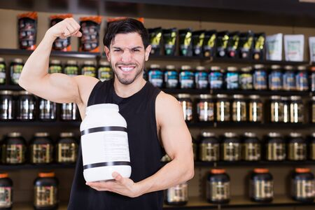 Young attractive muscular male showing his biceps and holding pot of sport nutrition