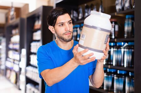 Serious efficient glad muscular man  choosing  sport nutrition products in shop