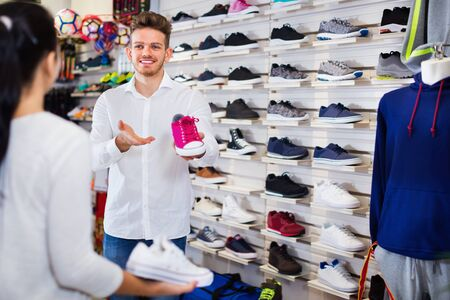 Young  friendly  man seller assisting girl in choosing sneakers in sports store Foto de archivo - 130051040